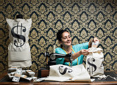 Tailor woman designing money bags for dollars