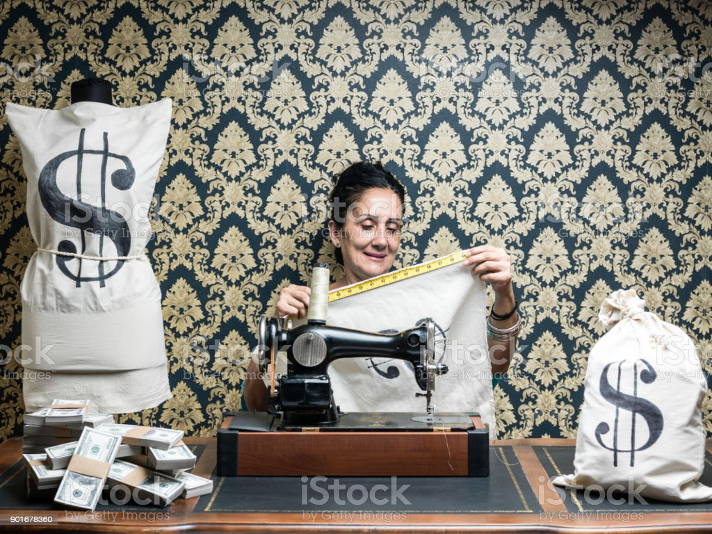 Tailor Woman Designing Money Bags For Dollars stock photo