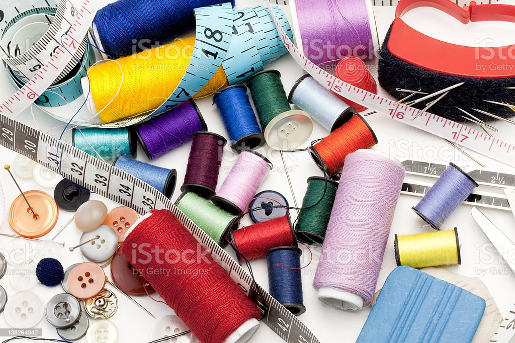 Tailor's Tools - threads, needle, buttons and measuring tapes stock photo