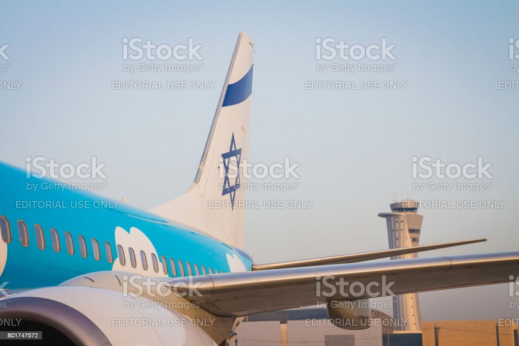 Tailplane of a El Al Up airline airplane with a drawing of the Israeli flag and the air traffic control tower of Ben Gurion Airport on sunrise