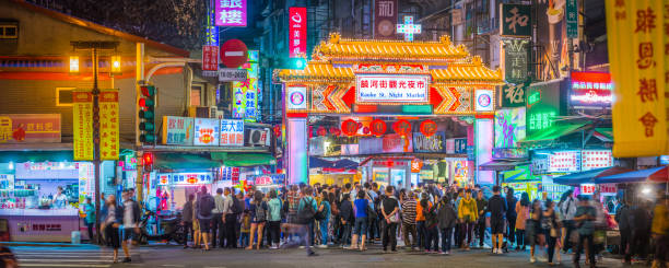 Taipei crowds of people Raohe St Night Market panorama Taiwan Crowds of shoppers and tourists at the neon lit entrance to Raohe Street Night Market in central Taipei, Taiwan's vibrant capital city. night market stock pictures, royalty-free photos & images