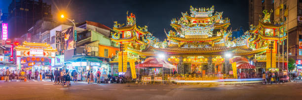 Taipei Songshan Ciyou Temple Raohe Street Night Market illuminated Taiwan Crowds of tourists and locals outside the ornate facade of Songshan Ciyou Temple and the entrance to Raohe Street Night Market illuminated at night in the heart of Taipei, Taiwan's vibrant capital city. night market stock pictures, royalty-free photos & images