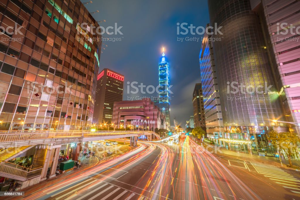 Taipei World Trade Center  in Xinyi Business District as traffic passes through a busy intersection at dusk stock photo