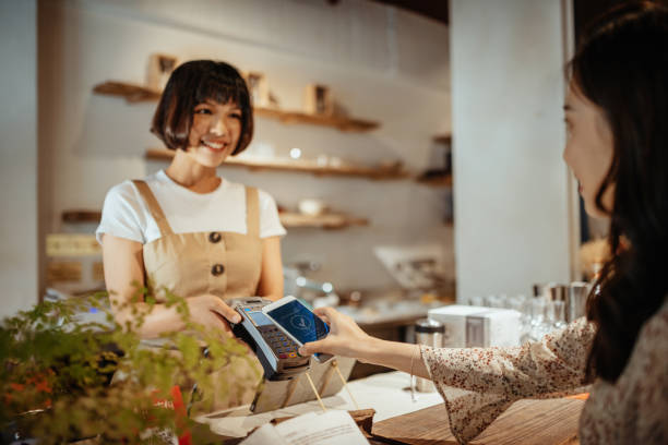taiwanese millennial women using contactless payment method - small business saturday stock pictures, royalty-free photos & images