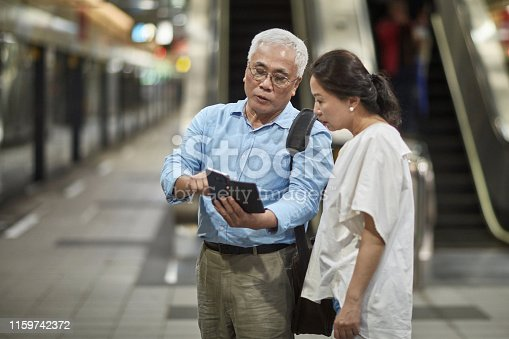 Experienced senior Asian travelers checking their smart phone for information about the next train departing from Taipei.