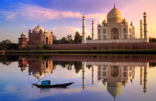 Taj Mahal Agra India at sunset with mirror reflection and vibrant sky. Taj Mahal is located at the banks of river Yamuna. Taj Mahal is a white marble mausoleum on the banks of the Yamuna river built by Mughal Emperor Shah Jahan. A UNESCO World Heritage site at Agra, India. Photograph taken from Mehtab Bagh. agra stock pictures, royalty-free photos & images