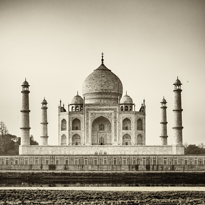 Famous Taj Mahal, the mausoleum located in Agra, India. It is one of the most recognizable structures in the world and is regarded as one of the eight wonders of the world. Black and White, Sepia toned image. Agra, India.