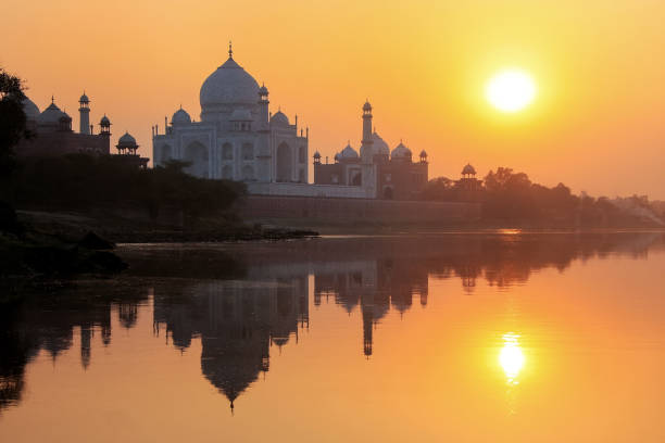 taj mahal reflected in yamuna river at sunset in agra, india - empire stock pictures, royalty-free photos & images