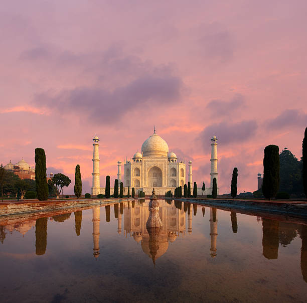 Taj Mahal Water Reflection Nobody Sunset Nobody present as Taj Mahal glows beautifully at sunset reflected in front garden water fountain pool of water under a dramatic pink sky in Agra, Uttar Pradesh, India. Plenty of copy space taj mahal stock pictures, royalty-free photos & images