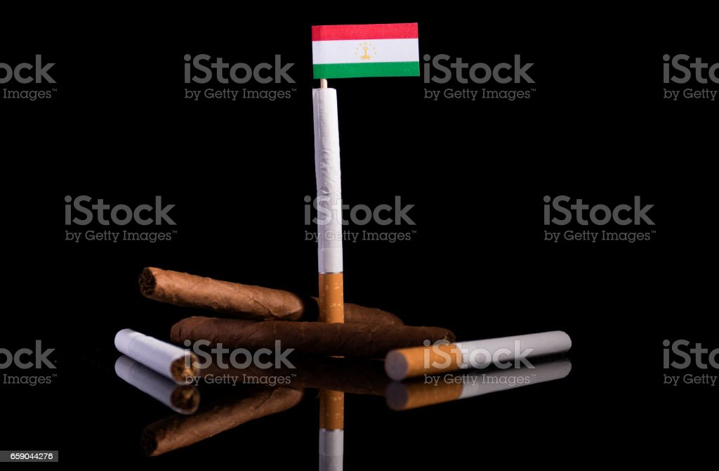 Tajikistan flag with cigarettes and cigars. Tobacco Industry concept. royalty-free stock photo