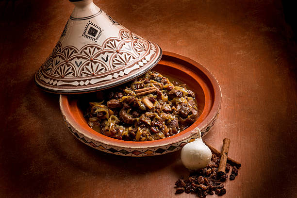 tajine with meat, onion, dried grape and cinnamon - tagine stock-fotos und bilder