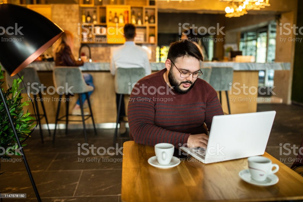Young, bearded, overweight male entrepreneur sitting in internet cafe...