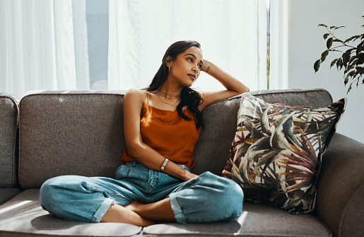 Shot of a young woman looking thoughtful while relaxing on the sofa at home