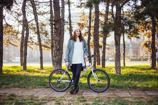 Take a deep breath Women riding bicycle in autumn park, weather is perfect for some recreation female biker resting stock pictures, royalty-free photos & images