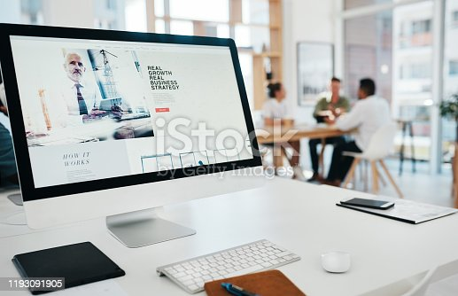 Cropped shot of a website page displayed on an office computer while businesspeople work in the background