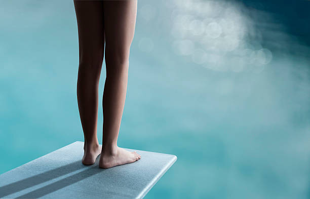Take a plunge Young boy or girl is standing on a diving board and ready to jump taking the plunge stock pictures, royalty-free photos & images