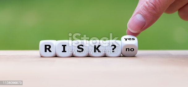 istock Take a risk? Hand turns a dice and changes the word