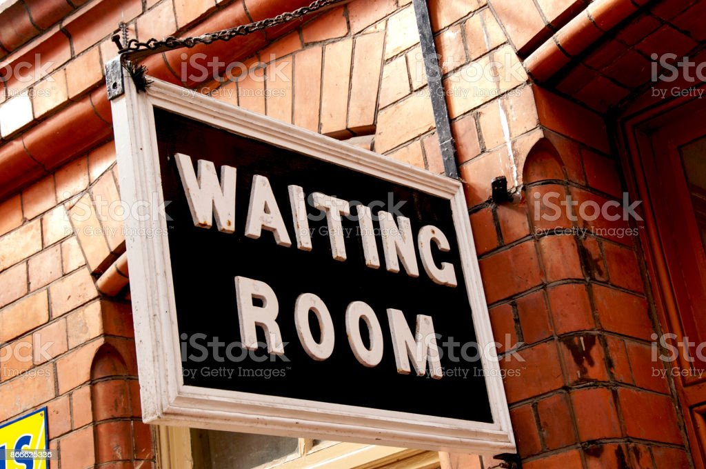 Take a seat Vintage waiting room sign at a traditional cotswold train station Architectural Feature Stock Photo