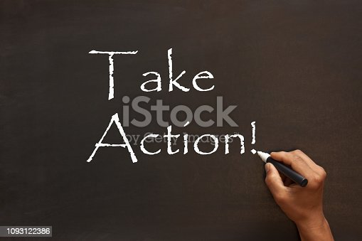 Take Action handwriting with white chalk marker on a blackboard. Business concept.