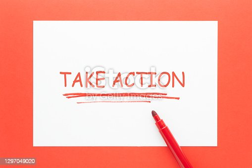 Take Action written on white paper sheet and red marker.