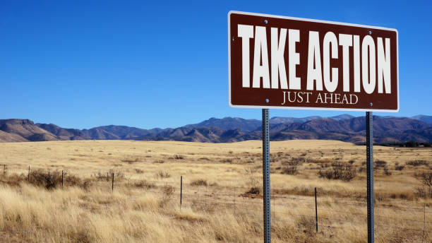 Take Action Just Ahead brown road sign Take Action Just Ahead brown road sign with blue sky and wilderness ASAP stock pictures, royalty-free photos & images