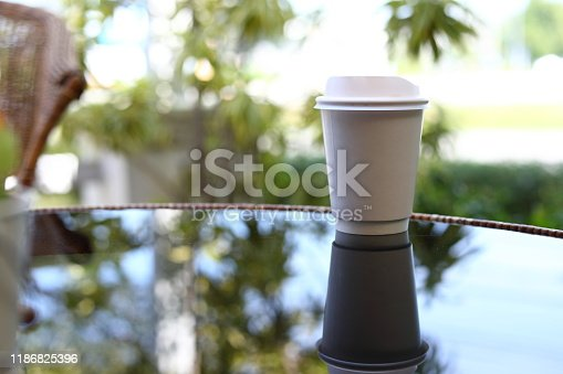 853676006 istock photo take away cup for hot coffee drink put on glass table inside garden cafe in the morning day 1186825396