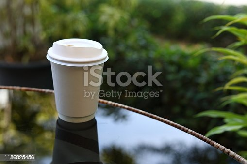 853676006 istock photo take away cup for hot coffee drink put on glass table inside garden cafe in the morning day 1186825456