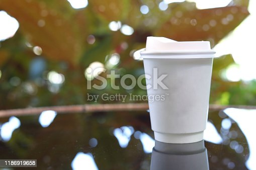 853676006 istock photo take away cup for hot coffee drink put on glass table inside garden cafe in the morning day 1186919658