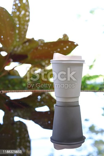 853676006 istock photo take away cup for hot coffee drink put on glass table inside garden cafe in the morning day 1188325653
