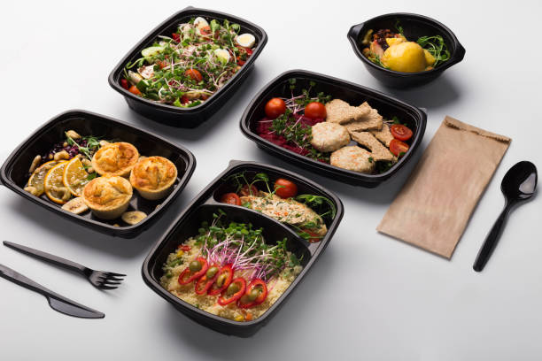 Take away food, variety of healthy meals top view Healthy lunch at workplace. Take away meals in black containers with cutlery on gray table food state stock pictures, royalty-free photos & images