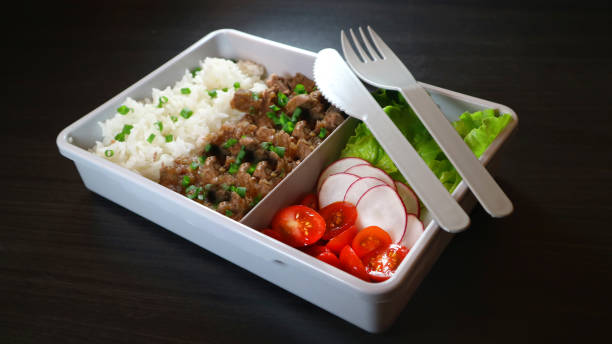Take away meal with rice, meat and salad. Meal prep on dark background. Ready to eat lunch with plastic knife and fork. stock photo