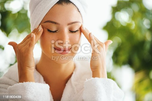 Young woman applying and rubbing anti age cream with her eyes closed. She's in the bathrobe and her hair is wrapped in the towel.