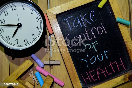 Take Care of Yourself on phrase colorful handwritten on chalkboard and alarm clock with motivation, inspiration and education concepts. Table background
