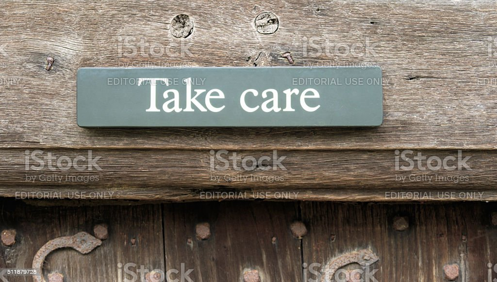 'Take Care' sign above a doorway stock photo