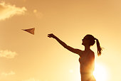 Woman throwing paper plane against a golden sunset.