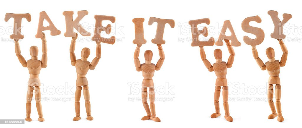 Take it easy - wooden mannequin holding this word royalty-free stock photo