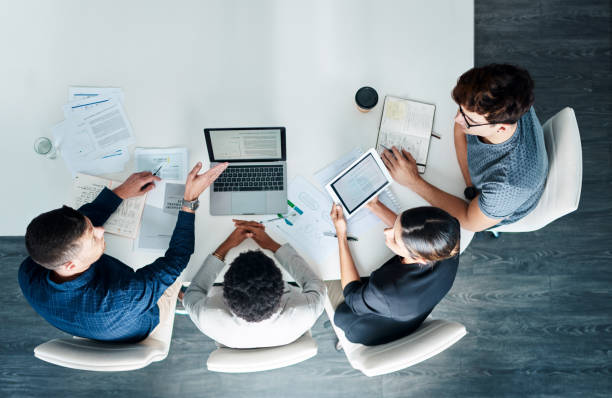 Take it to the top with teamwork High angle shot of a group of businesspeople having a meeting in a modern office aloft stock pictures, royalty-free photos & images
