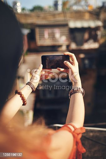 Cropped shot of a young woman taking pictures on her cellphone while out in the city