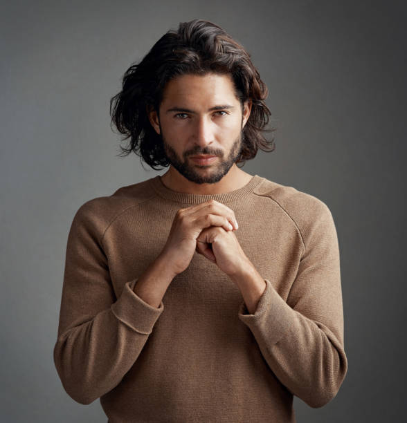 I take my spiritually very seriously Studio shot of a handsome young man praying against a gray background long hair stock pictures, royalty-free photos & images