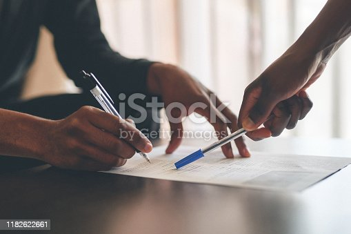 Cropped shot of an unrecognizable man filling a document with the help of a financial advisor at home