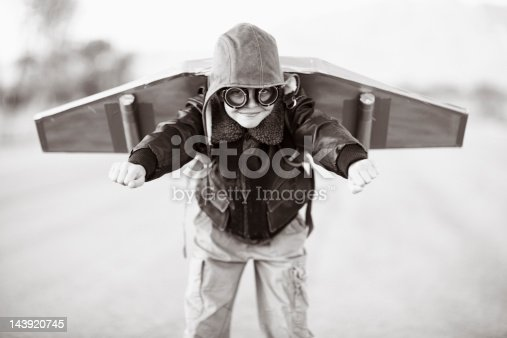 A young boy can't wait to fly the sky with his rocket pack. Sepia image.