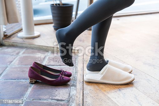 A woman who comes home and takes off her shoes and wears indoor slippers