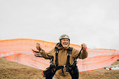 Photo of a smiling senior man ready for take off with his paraglider