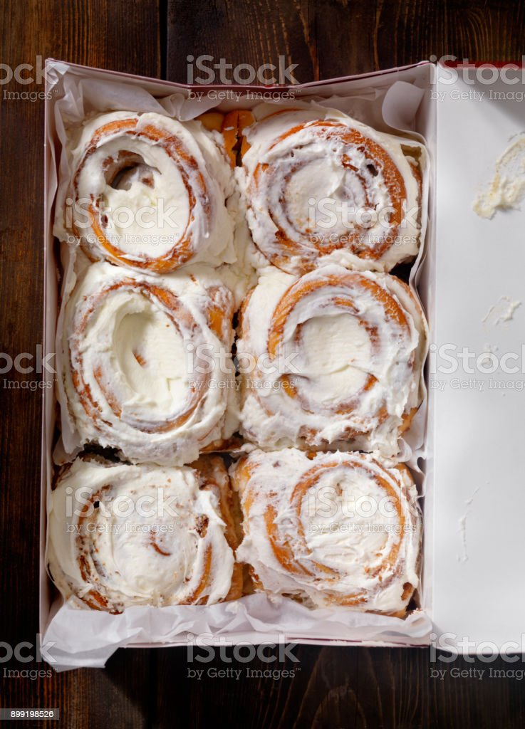 Take out Box of Iced Cinnamon Rolls on a Table