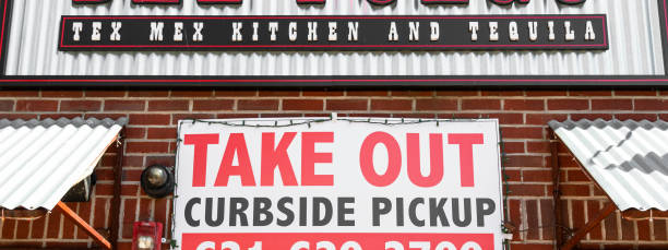 Take out curbside pickup sign posted on restaurant Babylon, New York, USA - 1 April 2020: Take out only with curbside pickup sign posted on a brick wall under avrestaurants sign due to coronavirus COVID 19 pandemic in Babylon, New York. curbsidepickup stock pictures, royalty-free photos & images