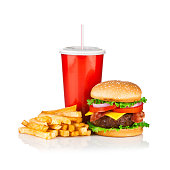 Cheeseburger, french fries and cola drink isolated on reflective white backdrop, typical combination for this meal. A red disposable cup of cola is in the center, the fries are laying at the left of the cola and a huge cheeseburger is at the right. The ingredients of the burger are a big beef portion, lettuce, bacon, tomato, and bacon on sesame seed bun.