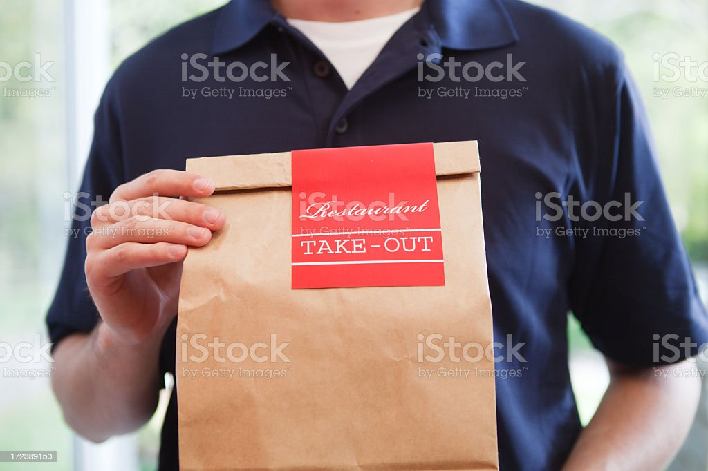 Take Out Food Delivery Person Holding Bag of Restaurant Dinner stock photo