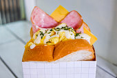 Close up healthy egg sandwich with ham & cheese inside white paper box container