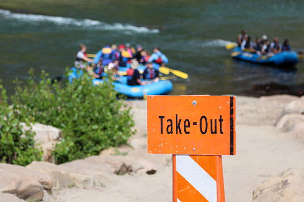 Take out sign on the Animas River with rafts Image of an orange take-out sign on the Animas River in Durango, Colorado.  Behind the sign, in the water are multiple blurry whitewater rafts filled with people. animas river stock pictures, royalty-free photos & images