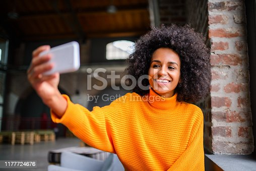 Young smiling woman taking a selfie at the coffee shop